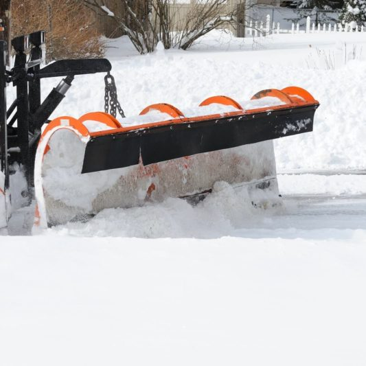 close up on snowplow removing snow in winter